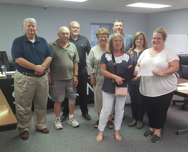 Robin Dudley and Karen Lawniczak of Swanton Shines present the group's donation for Christmas decorations in the village to Council on Aug. 12.