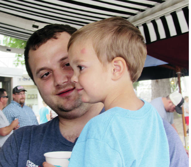 Robert Jablonski of Swanton and his son, Brycen, 3, wait for a treat at a food booth during this year's Fulton County Fair.