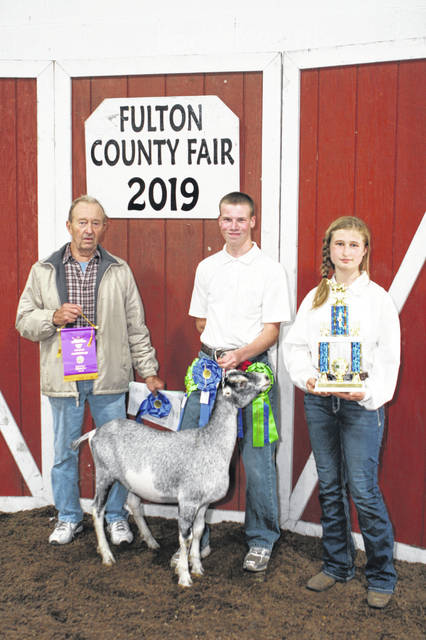 Grand Champion Market Dairy Goat Exhibitor: Elisha Michelson, (middle) son of Adrienne & Daniel of Delta (Leah Mishka holding trophy). Buyer: Beaverson Machine, represented by Ralph Beaverson.