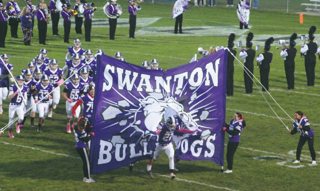Ian Saunders leads Swanton onto the field Friday before the Bulldogs' game against Delta.