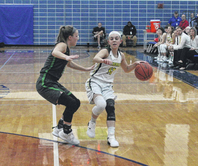 Mady Peluso of Evergreen, right, takes the ball up the court in a tournament game last winter. She was honorable mention all-league and in District 7 a season ago.