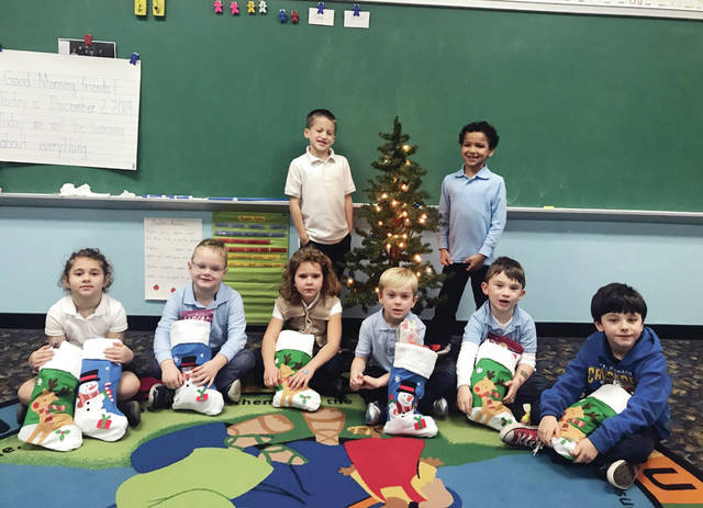 St. Richard School kindergarten students spread Christmas cheer to another continent when they stuffed stockings for soldiers earlier this month. The stockings were then mailed to Camp Humphreys in South Korea. Stuffing stockings for the soldiers were, from left and standing, Jacob Nichols-Eich and Madon Stuart, and sitting, Zoe Marsh, Jack Griggs, Sarah Thomas, Weston Blossom, Dylan Graves, and Jase Casier.