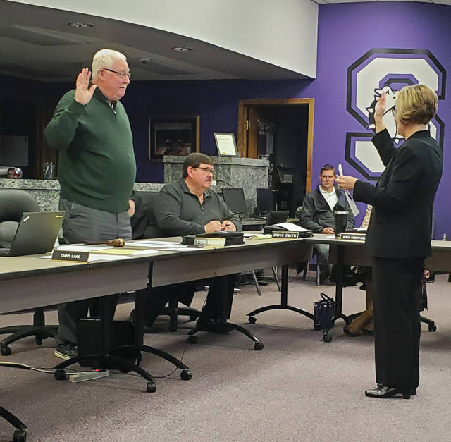 Steve Brehmer is sworn in as Swanton Board of Education President by Joyce Kinsman, treasurer.