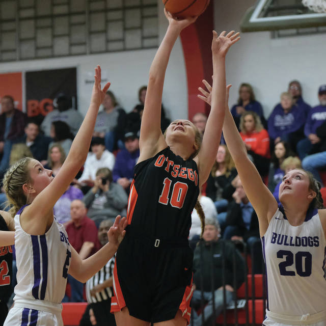 Otsego's Ellie Roberts shoots the ball between Swanton's Frankie Nelson, left, and Jessica Dohm Saturday night.