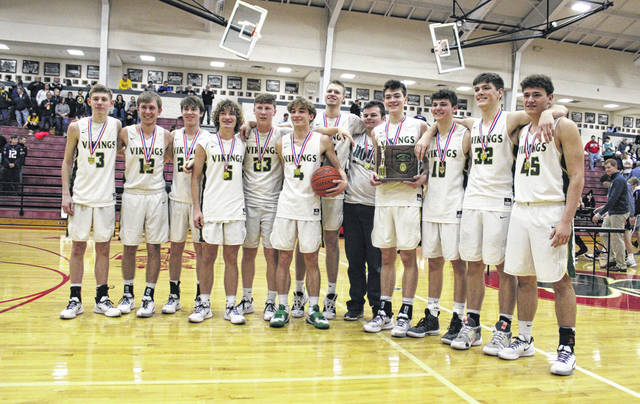 The Evergreen boys basketball team stands with the district trophy following a 42-39 win over NWOAL foe Archbold Saturday at Toledo Central Catholic. They also defeated Cardinal Stritch on Thursday, 44-43, following a bucket in the closing seconds by Evan Lumbrezer. It is the fourth district title for the program under longtime coach Jerry Keifer.