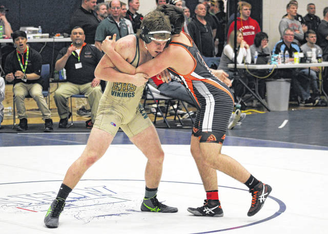 Logan York of Evergreen, left, locks up with his first round opponent on Friday at the district wrestling tournament. He finished 2-2 for the tournament, ending his season.