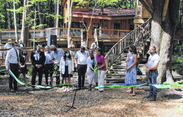 Linda Cannaley cuts the ribbon Wednesday morning at the grand opening ceremony for the Cannaley Treehouse Village at Oak Openings Metropark in Swanton.