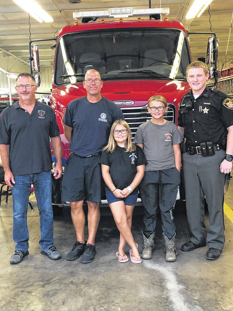 Cousins Brailynn Demoulin, center, and Sierra Lauharn, right, received commendations Aug. 10 from the Metamora Fire Department and the Fulton County Sheriff's Office for their part in rescuing an autistic youth from a neighborhood pond in June. Also pictured are Sheriff's Deputy Noah Eisel, MFD Chief Ray Kelble, far left, and Chad Jendrzejak, paramedic.