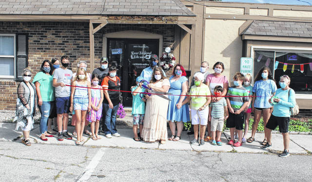 With family and friends present, owner Mandi Gineman cuts the ribbon for Sew Beyond Blessed Friday morning in Swanton. The business specializes in men's and women's alterations, but more services are also offered.