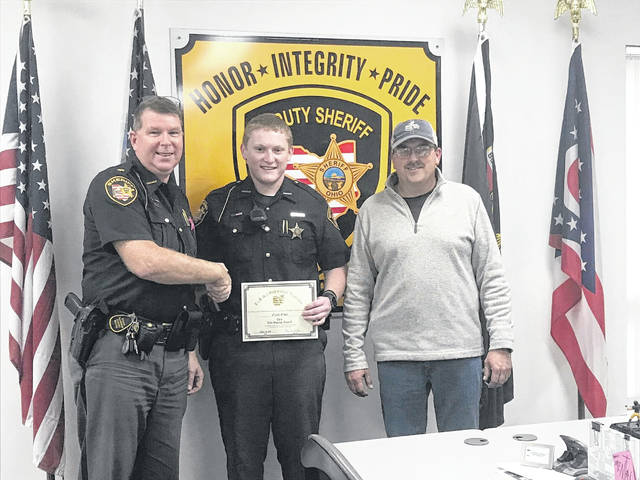 Fulton County Sheriff's Deputy Noah Eisel, center, was presented the Life Saving Award on Monday by Sheriff Roy Miller, left, for his role in saving the life of county resident Pete Dominique, right, who had collapsed and wasn't breathing. Eisel used an automated external defibrillator (AED) to revive Dominique with four shocks after responding to a 9-1-1 call placed from the home on Aug. 6 just before 10 p.m. The caller performed CPR on Dominique until Eisel arrived. The deputy was assisted by Delta, Wauseon, Swanton, and Metamora EMS.