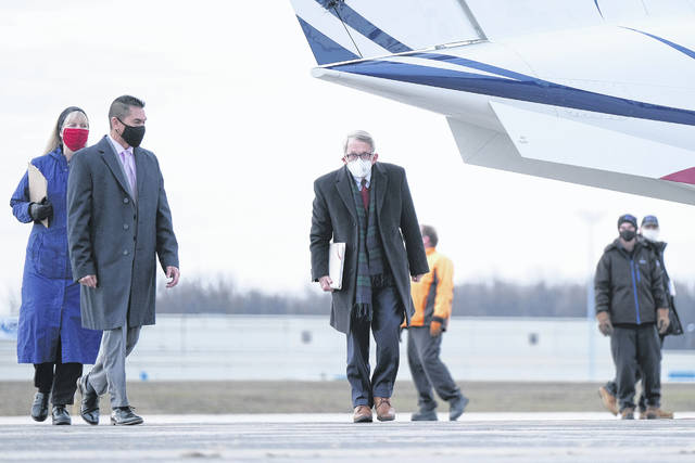 Ohio Gov. Mike DeWine, middle, walks away from a plane before the start of a press conference Wednesday morning at the Eugene F. Kranz Toledo Express Airportin Swanton.