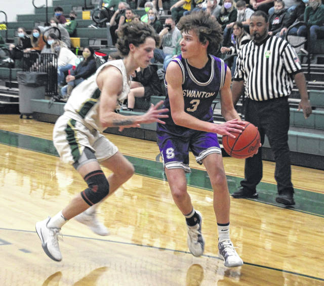 Lane Schoendorf of Evergreen guards Trent Weigel of Swanton during their game on Friday.