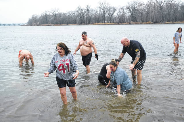 Revelers take a dip in the Maumee River near the Miltonville Fishing Access Friday afternoon.