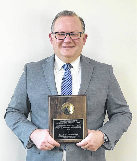 Fulton County Assistant Prosecuting Attorney Paul Kennedy poses with the 2020 Meritorious Assistant Prosecuting Attorney Award presented to him in December by the Ohio Prosecuting Attorneys Association. Kennedy received the award for his years of service to the county. He was nominated by Fulton County Prosecutor Scott Haselman. Each year, the OPAA awards one assistant prosecuting attorney in the state with the award. Kennedy is a 1994 graduate of the University of Toledo College of Law, and joined the Fulton County Prosecutor's Office in 1995. He has been the office's chief assistant for more than 10 years, and currently prosecutes the majority of the county's felony offenses.