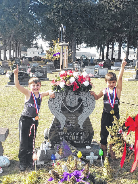 Brothers Masyn and Hudsyn Mitchell, of Swanton, rejoice with their late aunt Tiffany Mitchell after both won Biddy NWOAL championships in wrestling on Feb. 28.