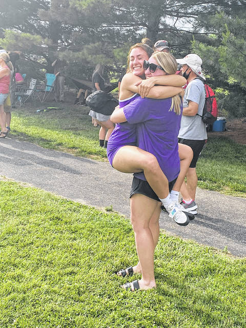 Swanton's Sami Taylor, left, embraces older sister Sidney Taylor, a previous state qualifier, upon qualifying for state in the shot put Thursday at the D-II Piqua Regional.