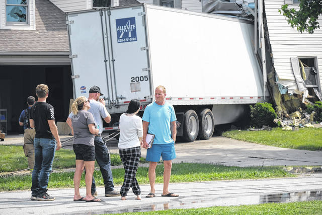 Shaun Downey, right, was home at the time a semi crashed into his home.