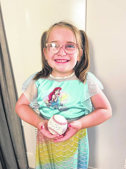 Abigail, the 6-year-old daughter of Fort Loramie graduate Kristin Courtney, holds a baseball autographed by her favorite player, Cincinnati Reds first baseman Joey Votto, following Saturday's game against the San Diego Padres.
