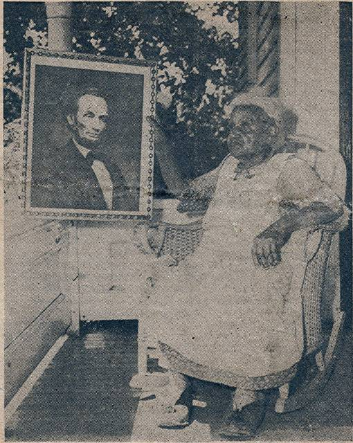 """""""Aunt Emma"""" Bard at the age of 88 with a picture of Abraham Lincoln, on the front porch of her home in Wauseon. Emma was born into slavery on a Boone County, Kentucky tobacco plantation owned by John L. Graves. When she was 15, the Civil War ended, and she became a Free Woman. She would continue to live in Boone County where she worked for various families making 25 cents a week. In 1884 she came north to Adrian, Michigan to put here children in school since no means of education was provided in Kentucky. In Adrian she met her husband Frank Bard and with him, would move to Fulton County and acquire a farm. They would be influential in the establishment of the Buelah United Methodist Church in Winameg. Her son, James Bard, graduated from Wauseon High School in 1914 and went on to become a doctor in Chicago."""