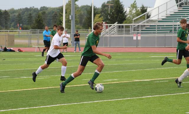 Riley Dunbar of Evergreen weaves his way through the Otsego defense during Tuesday's boys soccer match at Pifer Field. He had a goal in the Vikings' 5-0 win over the Knights.