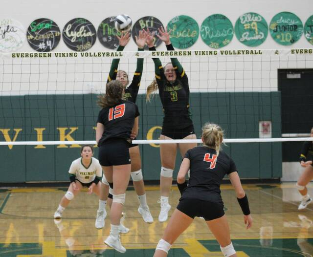 Lucy Serna and Nicole Johnson (3) of Evergreen go up in an attempt to block a shot hit by Liberty Center's Eliza Jones (13) Tuesday night. The Vikings won in straight sets over the Tigers.