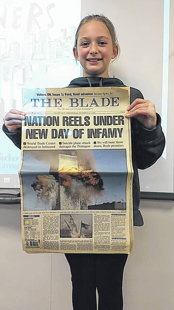 """Audrey Carte, Swanton seventh grader from the House of Gratus, brought in a Sept. 12, 2001 edition of the Toledo Blade to share during read aloud of the book, """"Towers Falling."""" Swanton Middle School is currently wrapping up an all school read aloud of the Jewell Parker Rhodes novel about a child whose family was affected by the 2001 terrorist attack."""