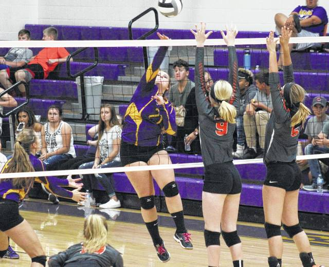 SHS senior Sydney Cleland (21) attempts a spike over a pair of Lady Eagles, during Southern's 3-0 win over Belpre on Tuesday in Racine, Ohio.