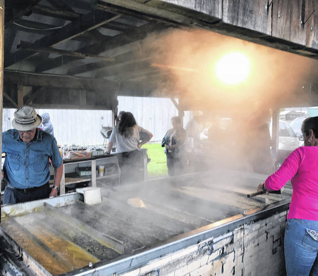 Steam rises as the molasses is made despite the rain at the Country Fall Festival on Sunday.