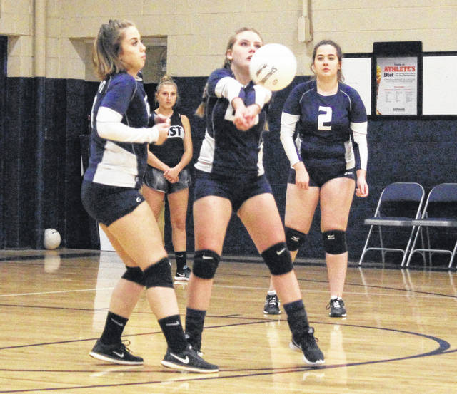 Hannan junior Pammie Ochs, middle, bumps a ball in the air during Game 1 of Tuesday night's volleyball match against Tolsia in Ashton, W.Va.