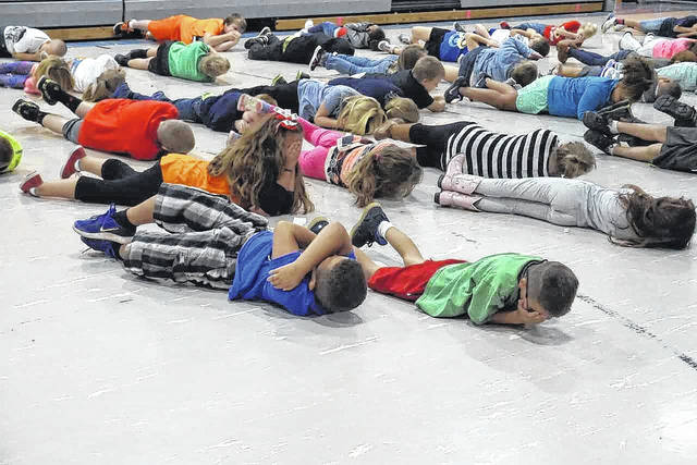 """Students are pictured as they practice """"Stop, Drop, and Roll"""" at New Haven Elementary School this week. The children are taught this technique in case their clothes catch on fire."""