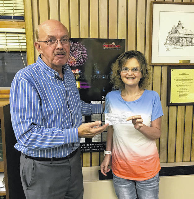 Mayor Brian Billings accepts a check from The Kitchen Table group, represented here by Mandy Spencer, for the construction of a splash pad at Krodel Park.