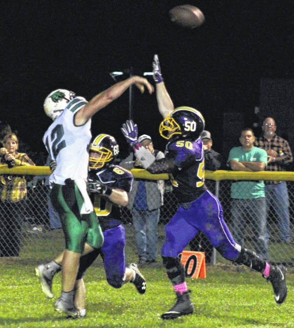 Southern juniors Sean Myers (60) and Alex VanMeter (50) put pressure on Waterford quarterback Peyten Stephens (12) during the Wildcats' 14-6 win on Friday in Racine, Ohio.