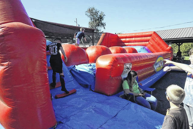 """""""Wipe Out"""" allowed children attending the Mason Harvest Festival to try out their ninja skills while jumping from ball to ball."""