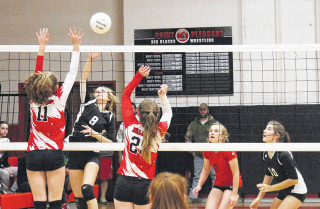 Point Pleasant's Madison Hatfield (8) goes up for a kill attempt over Wahama's Hannah Billups (11) and Lizzy Mullins (25) during Monday night's volleyball match in Point Pleasant, W.Va.