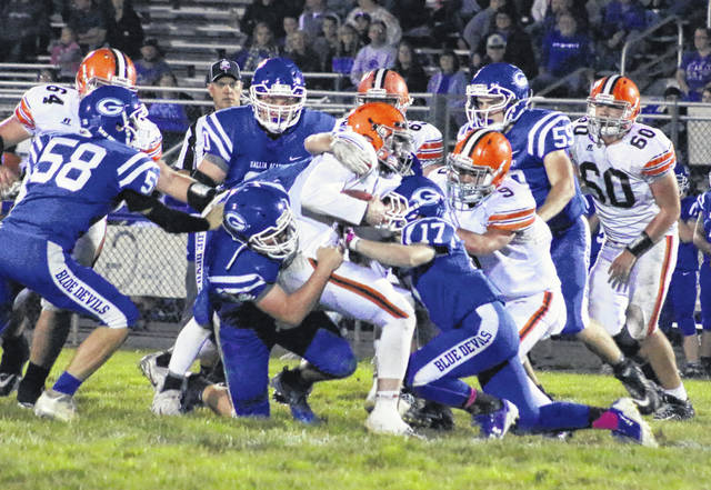 Gallia Academy defenders Cade Roberts and Trentin Waller (17) combine to bring down Ironton quarterback Gage Salyers during a first half run Friday night in a Week 9 OVC football contest at Memorial Field in Gallipolis, Ohio.