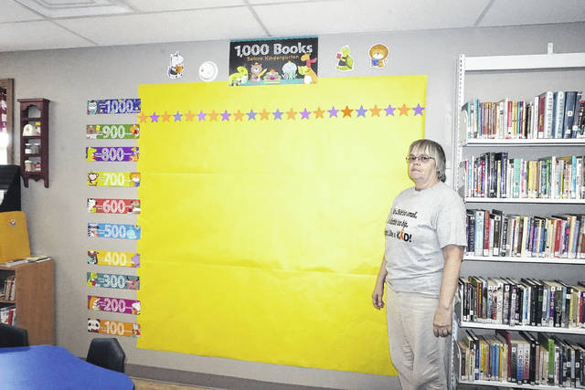 """Mason County Library Director Pam Thompson is pictured standing in front of the """"Wall of Fame"""" at the Mason library that will track the progress of preschoolers enrolled in the """"1,000 Books Before Kindergarten"""" program. The national program encourages parents to read 1,000 books to their child before starting school. Prizes will be given to the children at various intervals along the way."""
