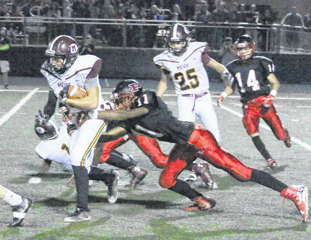 Meigs junior Jake Perry, left, runs with the football while dragging Point Pleasant defender Jovone Johnson (11) during the first half of a Week 8 gridiron contest in Point Pleasant, W.Va.