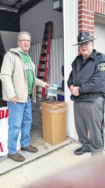 Tim Howard is pictured at left as he drops a bag of unused prescription pills into a container Saturday during the 14th National Prescription Drug Take Back Day. Local drop off points were located in both Point Pleasant and New Haven. Also pictured is Mason County Sheriff's Deputy Grant Hysell.