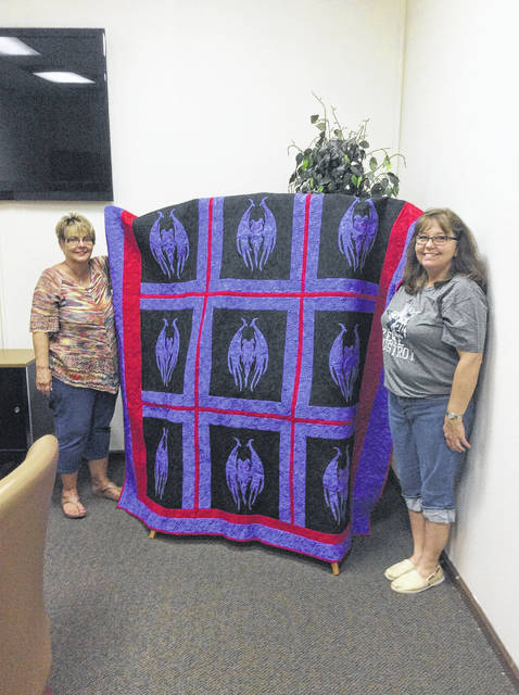 Marcia Nibert, on the left, with Cathy Neville of the Battle Days committee displaying the quilt made by Willanna Wales.