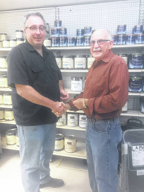 Jack Lee, at right, passes the keys to Paint Plus Hardware's new owner, Craig Herdman.