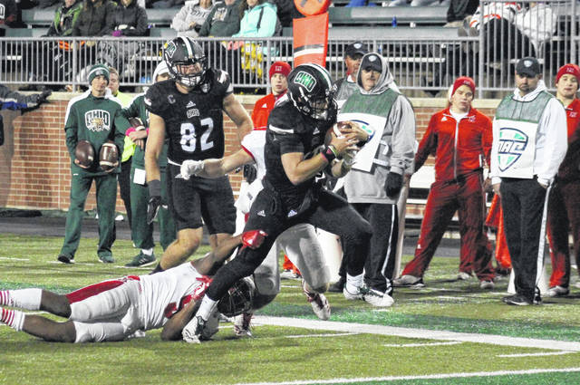Ohio sophomore Nathan Rourke breaks away from a pair of RedHawks, in front of OU senior Troy Mangen (82), during a first half touchdown run on Tuesday in Athens, Ohio.