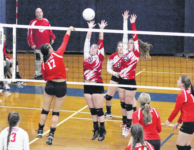 Wahama seniors Madison VanMeter (10) and Elizabeth Mullins (25) both leap for a block attempt during Game 1 of Tuesday night's Class A Region IV, Section 1 volleyball match against Calhoun County at Parkersburg Catholic High School.