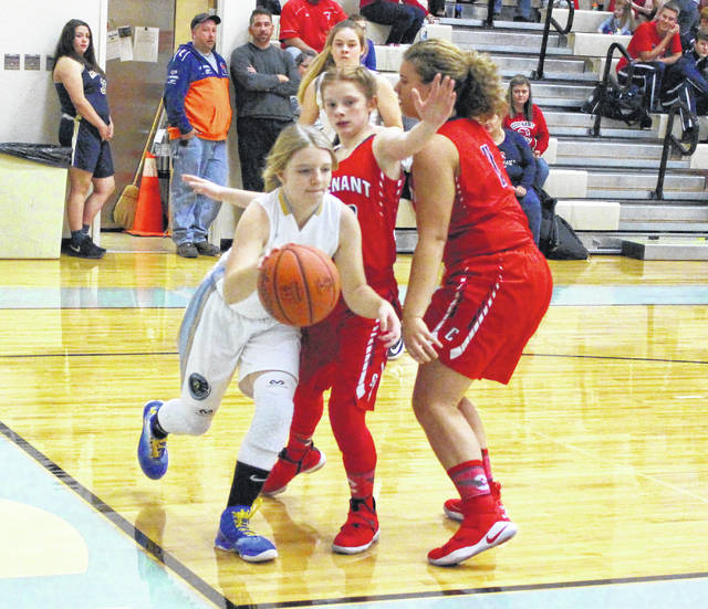 Ohio Valley Christian freshman Lauren Ragan dribbles past a pair of Covenant defenders during the first half of Tuesday night's girls basketball contest in Gallipolis, Ohio.