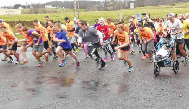 Runners take off at the start of the Keep Your Fork 5K road race.
