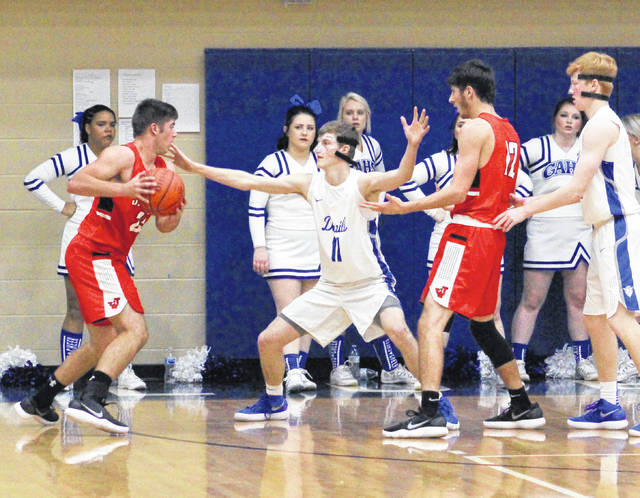 Gallia Academy junior Blaine Carter (11) defends a Jackson player during the first half of Saturday night's non-conference boys basketball contest in Centenary, Ohio.