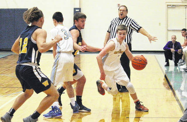 Ohio Valley Christian sophomore Arden Peck (right) runs off of a screen set by classmate Levi Anderson (34), during the Defenders' 65-19 loss on Tuesday in Gallipolis, Ohio.