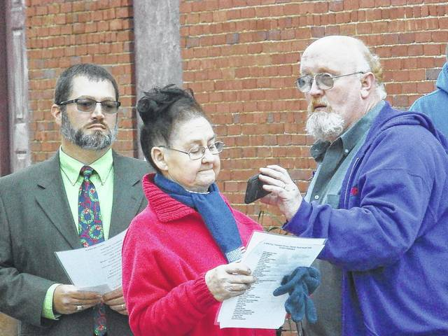 The late Carolin Harris, pictured at center, is shown reading the names of the victims of the Silver Bridge collapse at a memorial held two years ago. Her son and his father were killed on the bridge. This Friday, national, state and local speakers will present a program to observe the 50th anniversary of the Silver Bridge Tragedy.
