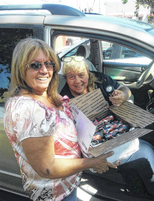 Carolyn Montañez, seated, helps pass out lights in Puerto Rico, seen here handing a box of lights to a member of Rotary Club Ciales.