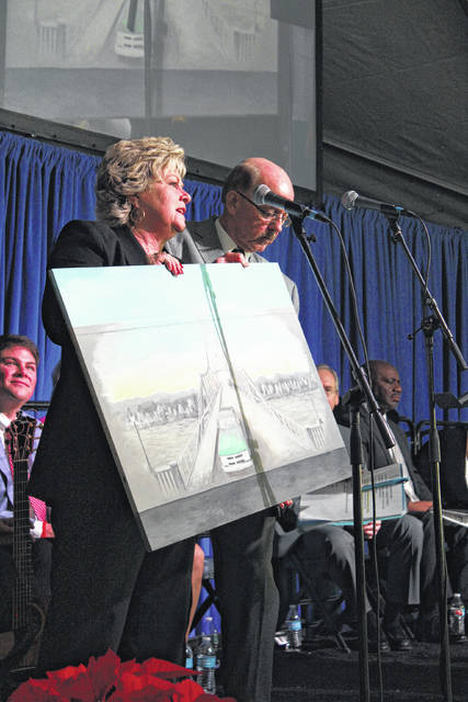 Mason County Commission President Tracy Doolittle and Point Pleasant Mayor Brian Billings unveil an artistic rendering of a flood wall mural which will be placed on the flood wall panel where the Silver Bridge entered at 6th Street.