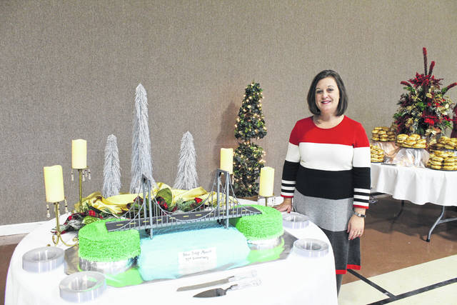 Heidi Wood, known for her customized cakes, poses with her special creation for the reception held following the Silver Bridge Memorial Ceremony.